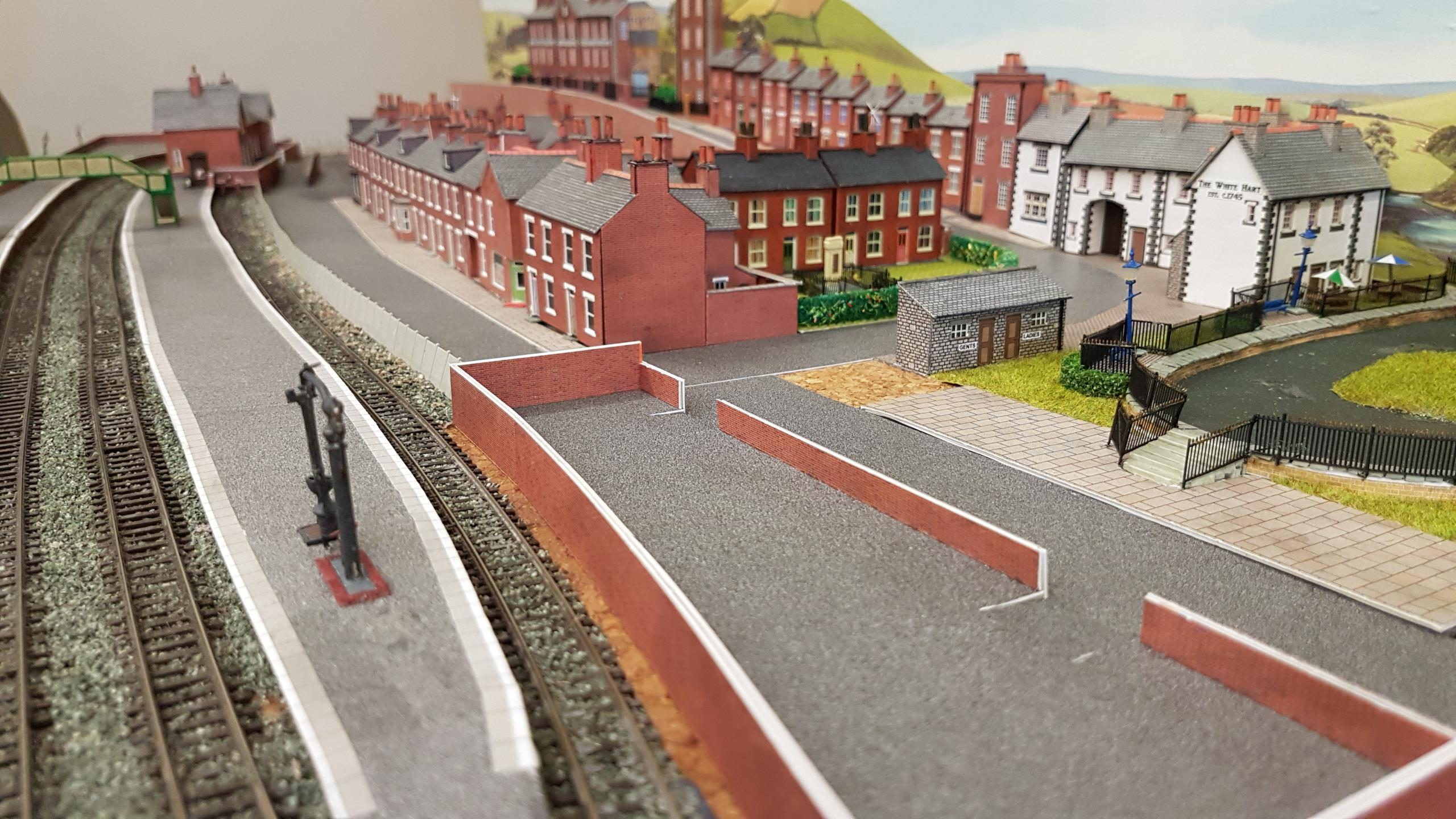 N gauge Ospringe St Peter & Water Lane upper main line station platforms. Station road houses and buildings behind them take shape. The area in the foreground is to become a garage with petrol pumps.